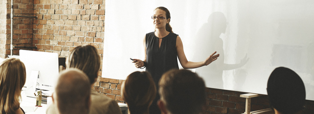 A woman stood at the front of a class presenting